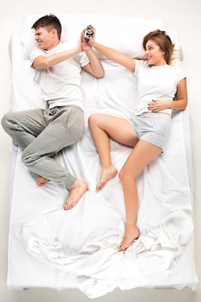 O jovem casal adorável, deitado em uma cama com despertador