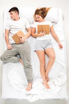O jovem casal adorável, deitado em uma cama com livros