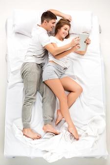 O jovem casal adorável, deitado em uma cama com o laptop