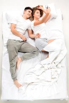 O jovem casal adorável, deitado em uma cama