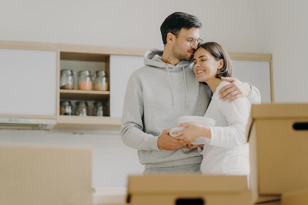 O jovem casal apaixonado abraça e beija com ternura, segura a pilha de pratos brancos, fica na cozinha durante o dia da mudança, cercado por muitas caixas cheias de pertences pessoais, desembale as coisas
