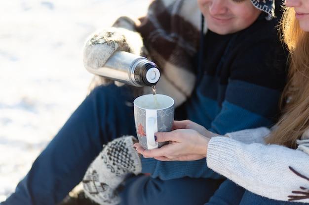 O jovem casal apaixonado bebe uma bebida quente de uma garrafa térmica, sentado no inverno na floresta, enfiado em tapetes quentes e confortáveis e aprecia a natureza. o cara derrama uma bebida de uma garrafa térmica em um copo