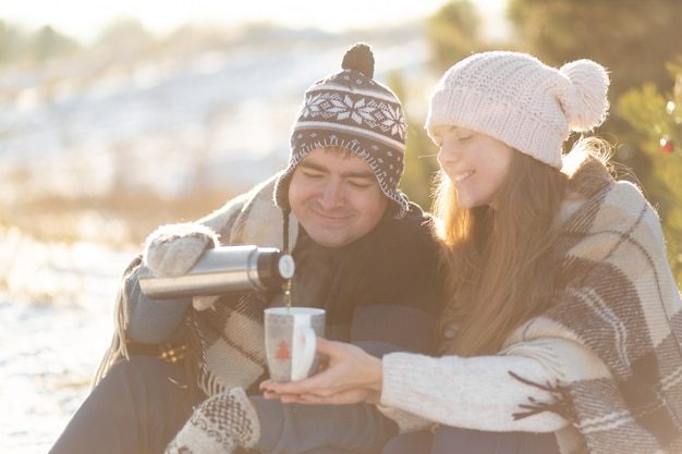 O jovem casal apaixonado bebe uma bebida quente de uma garrafa térmica, sentado no inverno na floresta, enfiado em tapetes quentes e confortáveis e aprecia a natureza