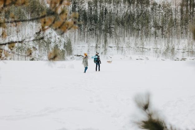 O jovem casal com cão haski no parque natural da floresta no inverno. conceito de aventura de viagem