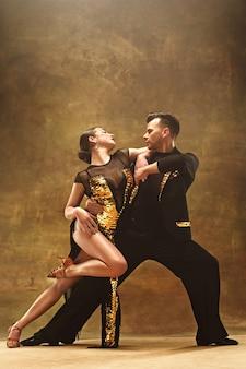 O jovem casal de dança de salão com vestido de ouro dançando em pose sensual no fundo do estúdio. dançarinos profissionais dançando tango. conceito de dança de salão. emoções humanas - amor e paixão