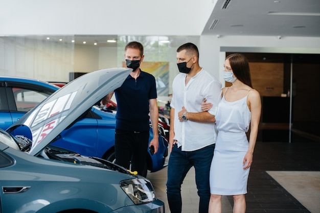 O jovem casal de máscaras seleciona um veículo novo e consulta um representante da concessionária no período da pandemia. vendas de carros e vida durante a pandemia.