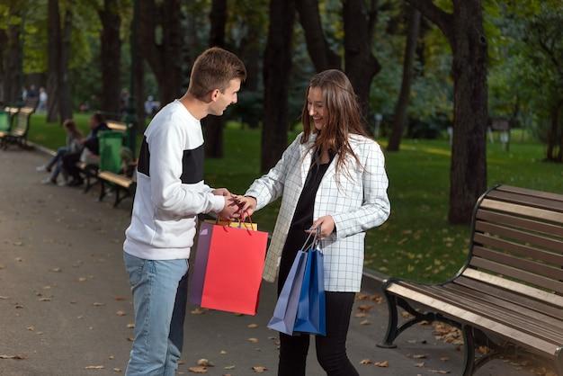 O jovem casal é divertido e está pensando em fazer compras. sacos de papel colorido nas mãos.