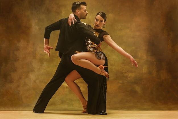 O jovem casal em pose sensual no fundo do estúdio. dançarinos profissionais dançando tango