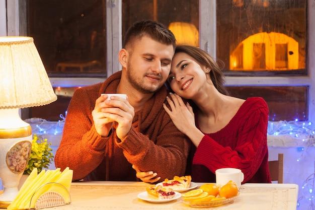 O jovem casal feliz com xícaras de chá e bolos.