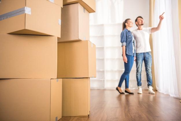 O jovem casal feliz olhando em volta de seu novo apartamento.