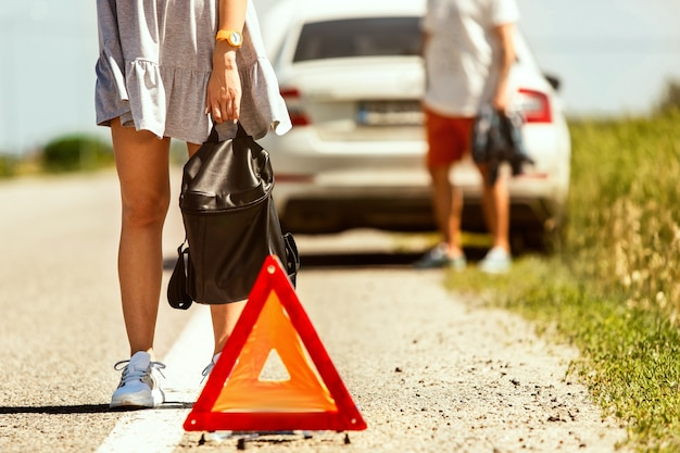 O jovem casal quebrou o carro durante uma viagem para descansar. eles estão tentando parar outros motoristas e pedir ajuda ou pedir carona. relacionamento, problemas na estrada, férias.