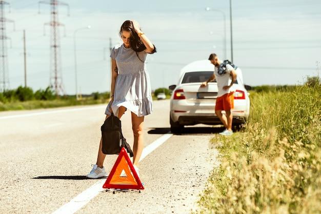 O jovem casal quebrou o carro durante uma viagem para descansar. eles estão tentando parar outros motoristas e pedir ajuda ou pedir carona