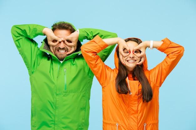 O jovem casal surpreso no estúdio em jaquetas de outono isoladas em azul.