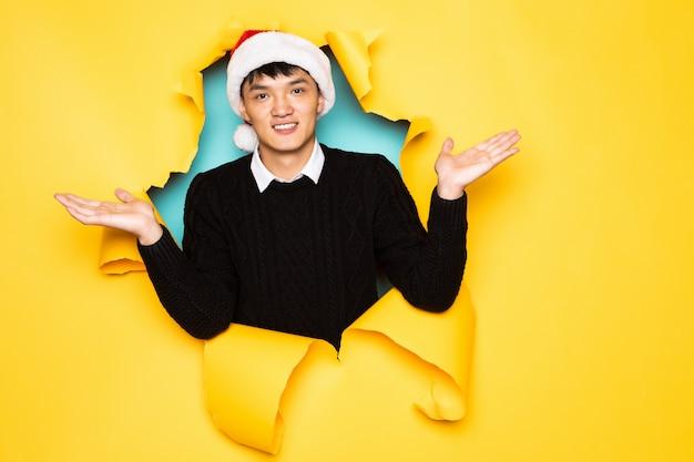 O jovem chinês com chapéu de papai noel e mãos levantadas mantém a cabeça no buraco da parede amarela rasgada. cabeça masculina em papel rasgado.