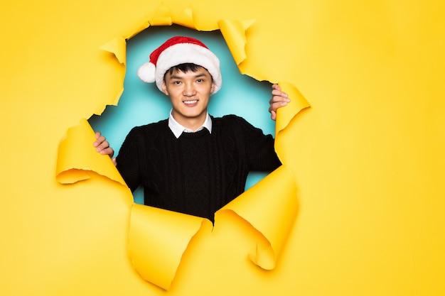 O jovem chinês com chapéu de papai noel mantém a cabeça no buraco da parede amarela rasgada. cabeça masculina em papel rasgado.