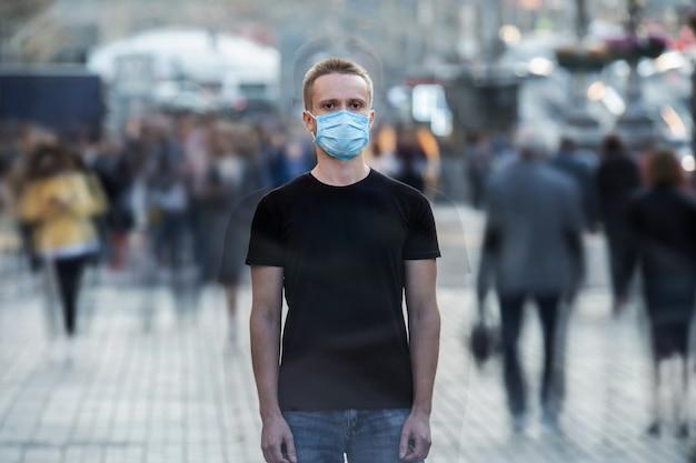 O jovem com máscara médica no rosto está em pé na rua urbana