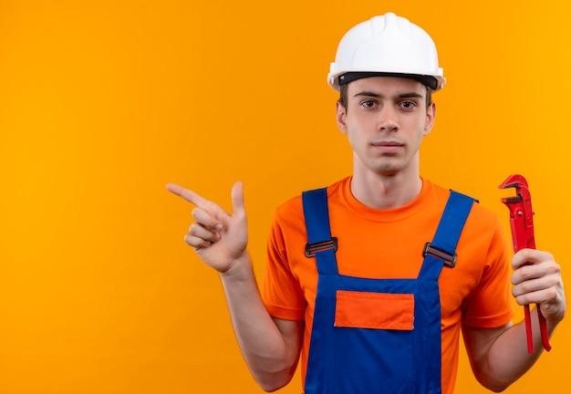 O jovem construtor usando uniforme de construção e capacete de segurança segura um alicate de ranhura e aponta para a esquerda com o polegar