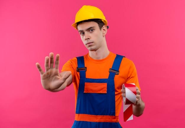 O jovem construtor, vestindo uniforme de construção e capacete de segurança, segura um sinal vermelho e branco e mostra a parada com a mão