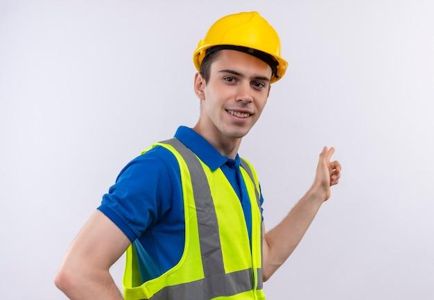 O jovem construtor vestindo uniforme de construção e capacete de segurança, sorri e mostra além