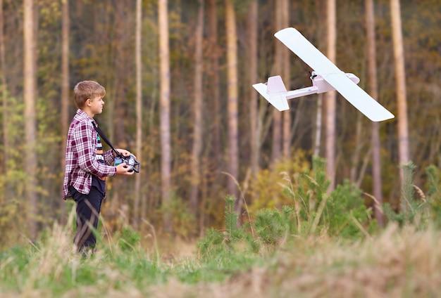 O jovem controla uma aeronave controlada por rádio de sua própria montagem.