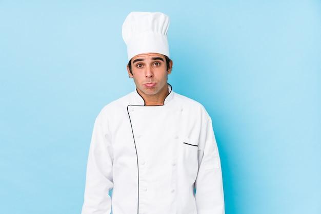 O jovem cozinheiro homem encolhe os ombros e abre os olhos confusos.