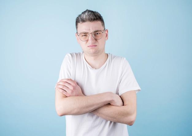 O jovem cruzou os braços com nojo no rosto contra uma parede azul