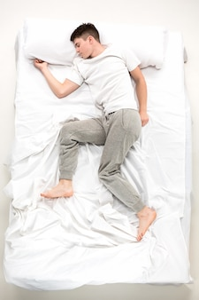 O jovem deitado em uma cama