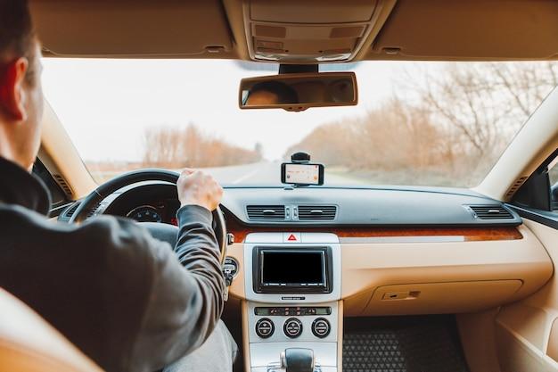 O jovem dirigindo um carro moderno em estrada de asfalto