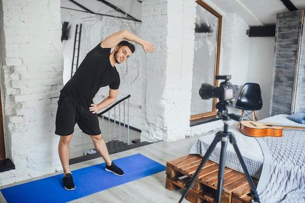 O jovem e bonito blogueiro de fitness grava um vídeo para seu blog e mostra como fazer a inclinação certa para o lado, em uma sala estilo loft