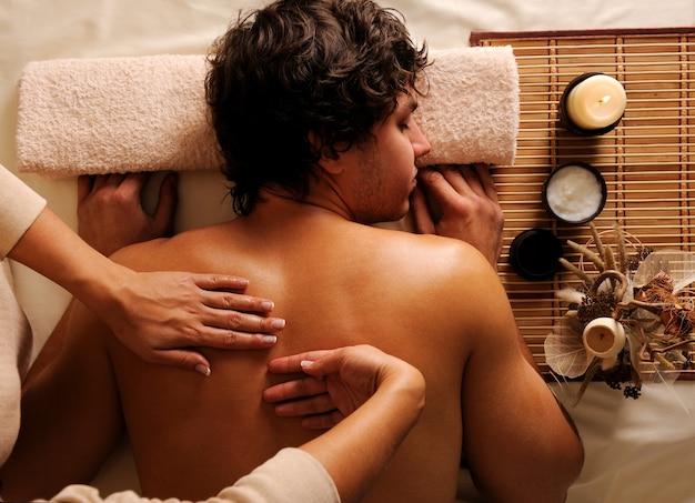 O jovem em relaxamento, recreação, massagem saudável em um salão de beleza. visão de alto ângulo. luz baixa