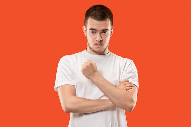 O jovem emocional irritado gritando em um espaço laranja