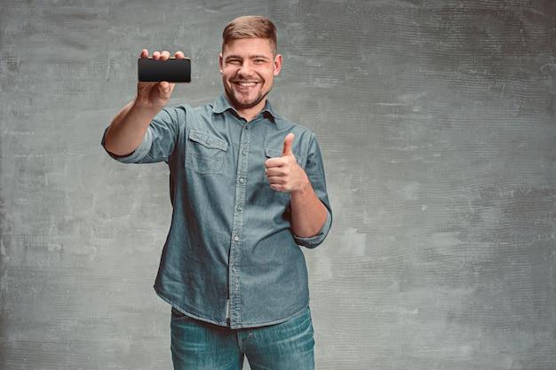 O jovem empresário caucasiano sorridente na parede cinza com telefone