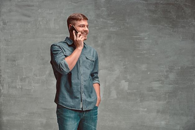 O jovem empresário caucasiano sorridente no espaço cinza, falando com telefone