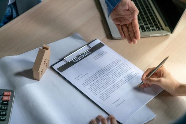 O jovem empresário e o cliente comprador da casa alcançaram juntos os meios-alvo e assinaram o contrato de venda de imóveis
