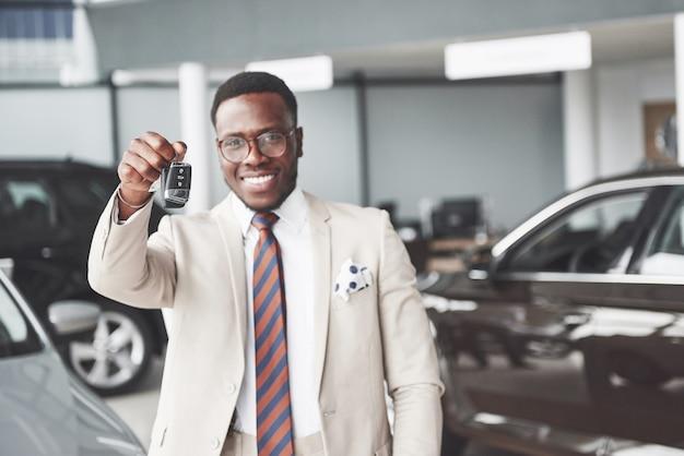O jovem empresário negro e atraente compra um carro novo, ele tem as chaves na mão. sonhos se tornam realidade