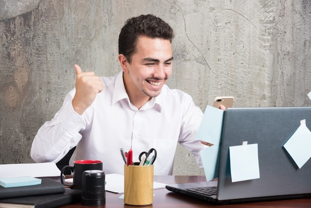 O jovem empresário recebeu boas notícias na mesa do escritório. Foto gratuita