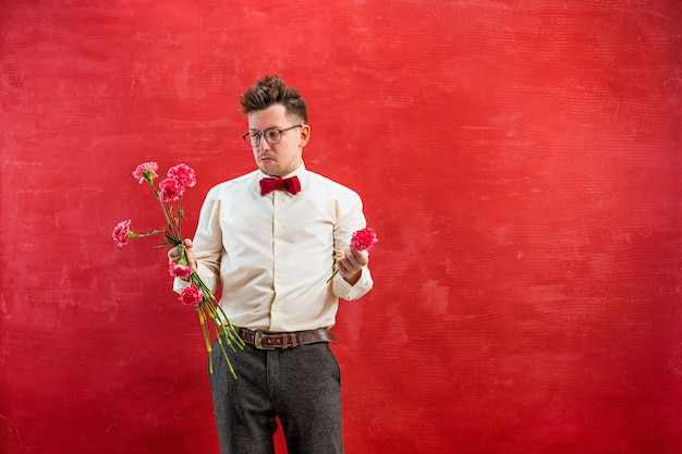 O jovem engraçado com buquê quebrado em fundo vermelho studio. conceito - amor infeliz