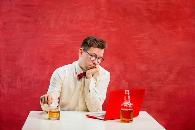 O jovem engraçado com conhaque, sentado com o laptop no dia de são valentim no estúdio vermelho.