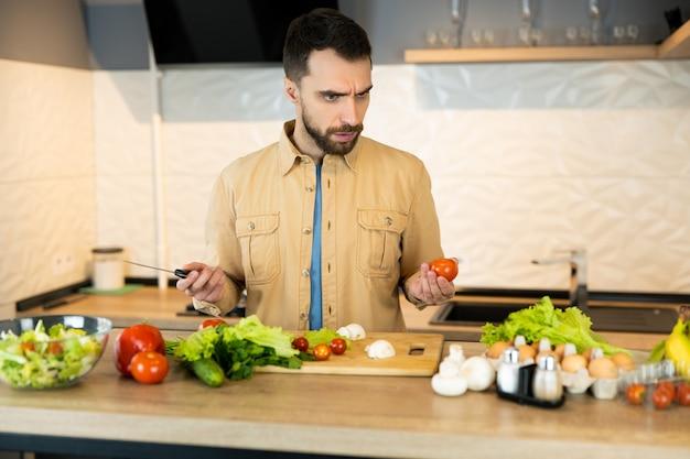 O jovem está curioso para cozinhar salada vegetariana. homem bonito não sabe o que cozinhar
