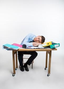 O jovem está dormindo na mesa durante seu horário de trabalho