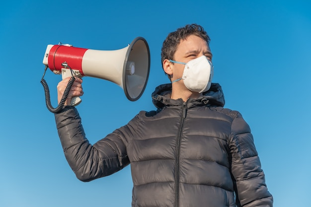 O jovem está ouvindo novas informações e notícias do megafone sobre a epidemia de coronavírus no mundo