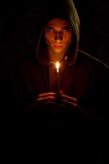 O jovem está segurando uma vela velha que ilumina a escuridão.