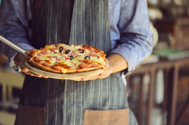 O jovem está servindo pizza quente.