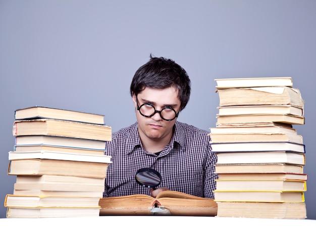O jovem estudante com os livros isolados.