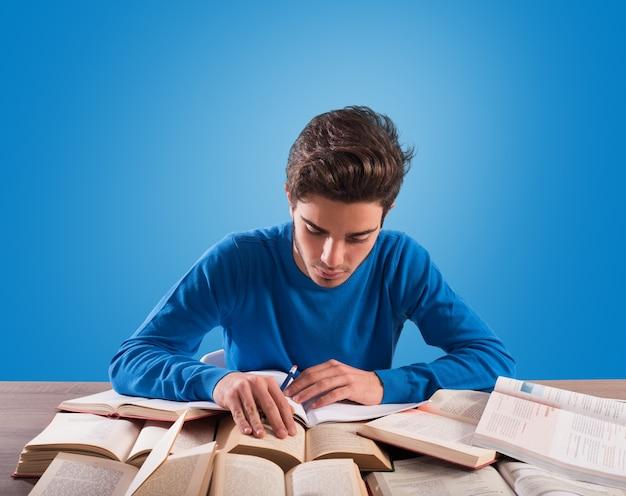 O jovem estudante está estudando muito na mesa