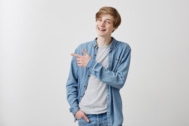 O jovem europeu de cabelos louros tem uma expressão intrigante e alegre, indica com o dedo da frente no espaço da cópia, diz: olha isso! macho amigável em poses de roupas jeans