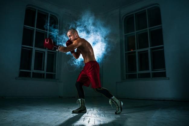 O jovem fazendo kickboxing na fumaça azul