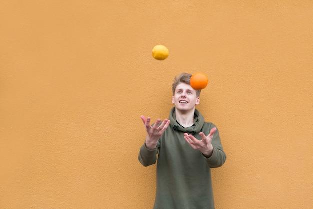 O jovem feliz faz malabarismos com laranja e limão contra a parede de uma parede laranja.