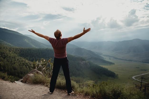 O jovem fica em uma pedra e olha para o vale. trekking nas montanhas