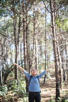 O jovem hipster, mulher feliz, aprecia a natureza na floresta com os braços estendidos.